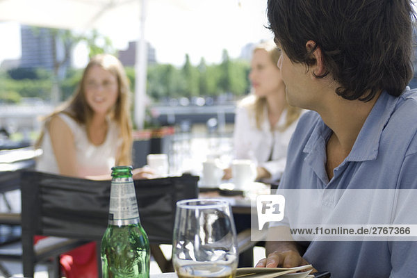 Junger Mann sitzt draußen im Café und schaut über die Schulter zu den jungen Frauen  die hinter ihm sitzen.