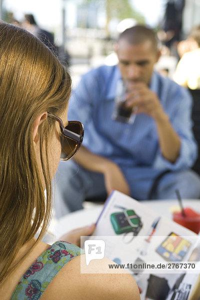 Junge Frau sitzt in einem Straßencafé  liest Katalog  über die Schulter gesehen