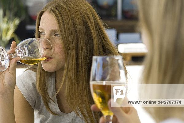 Junge Frauen trinken Bier in einem Outdoor-Café