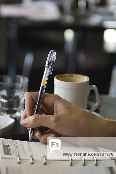 Frau sitzt im Café  schreibt in der Tagesordnung  Blick auf die Hand abgeschnitten