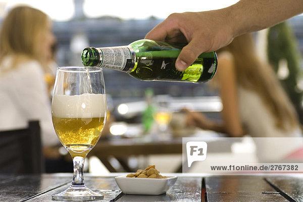 Bier ins Glas gießen im Straßencafé