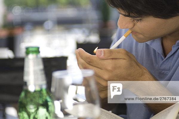 Junger Mann beim Anzünden einer Zigarette