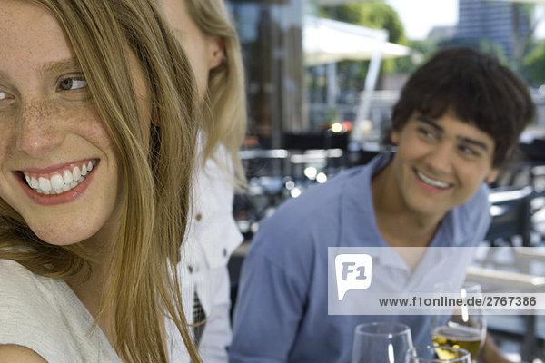 Junge Freunde sitzen auf dem Bürgersteig  schauen über die Schultern und lächeln