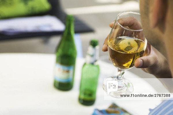 Mann trinkt Bier aus einem Glas  abgeschnitten  über die Schulter gesehen