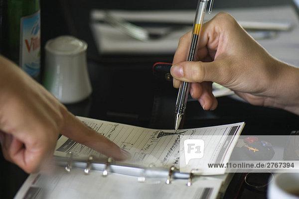 Zwei Leute  die Pläne mit der Agenda machen  eine hält den Stift  die andere zeigt auf die Seite.