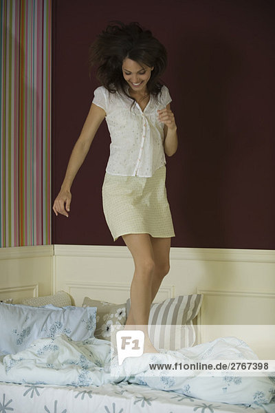 Young woman jumping on bed  full length