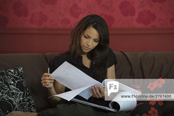 Junge Frau auf Sofa sitzend  Lesedokument