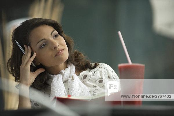 Frau sitzend im Café mit Notizbuch  Kopf haltend