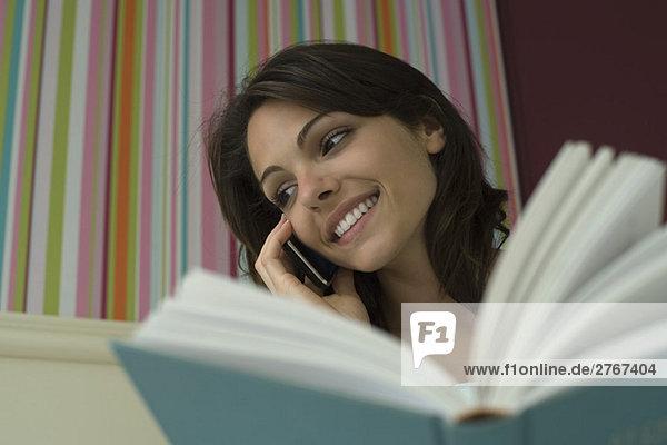 Frau  die das Buch hält und das Handy benutzt  mit niedrigem Blickwinkel