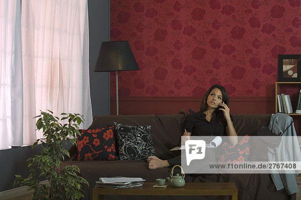 Frau sitzt auf dem Sofa  benutzt das Handy und hält das Dokument auf dem Schoß.