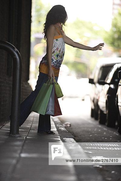 Junge Frau ruft Taxi  trägt Einkaufstaschen.