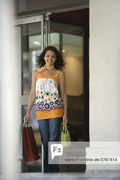Young woman leaving store with shopping bags  smiling at camera