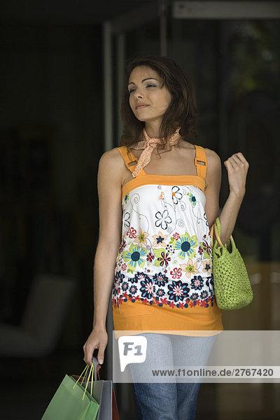 Junge Frau mit Einkaufstaschen  lächelnd  wegschauend
