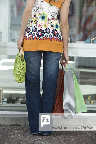 Junge Frau beim Schaufensterbummel  mit mehreren Einkaufstaschen  zugeschnittene Rückansicht