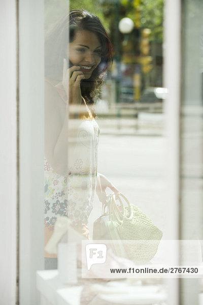 Frau schaut ins Schaufenster  spricht mit dem Handy