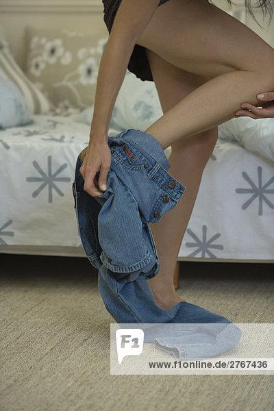 Frau beim Ausziehen der Jeans  abgeschnitten  Blickwinkel niedrig