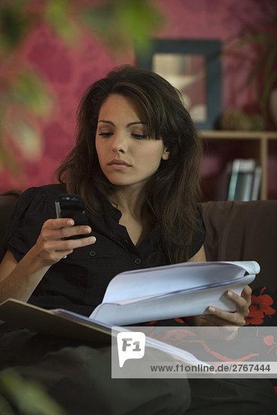 Frau sitzt auf dem Sofa mit Dokument und schaut auf das Handy.