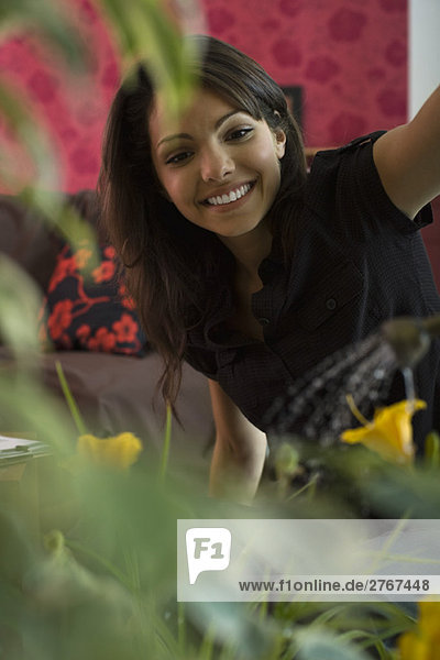 Junge Frau lächelt blühende Zimmerpflanze an