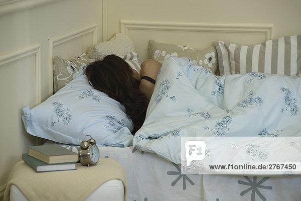 Junge Frau schläft im Bett  Rückansicht