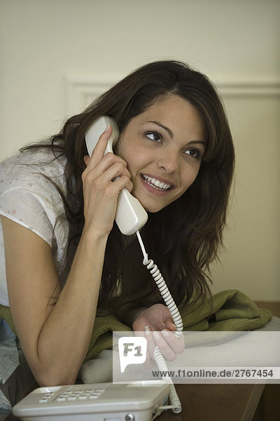 Junge Frau mit Festnetztelefon  lächelnd