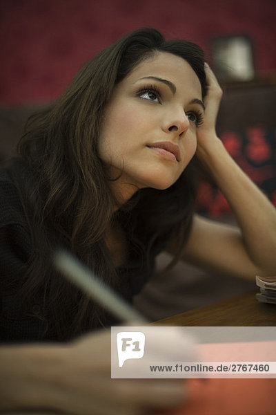 Junge Frau beim Schreiben  in Gedanken aufblickend