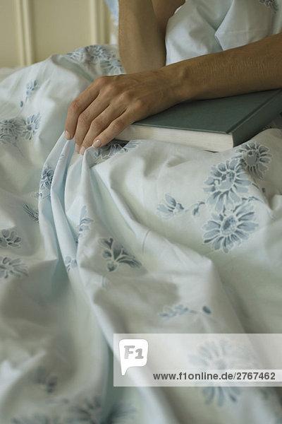 Frau im Bett sitzend mit der Hand auf dem Buch liegend  Ausschnittansicht