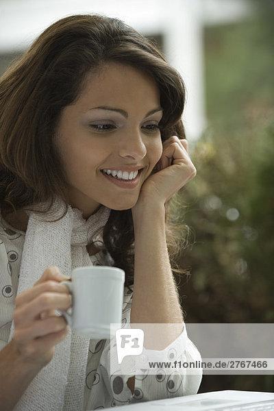 Junge Frau trinkt Kaffee und schaut auf Laptop-Computer