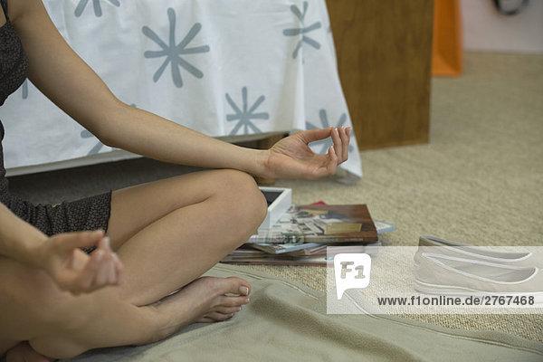 Frau sitzend in Lotusstellung  Ausschnittansicht