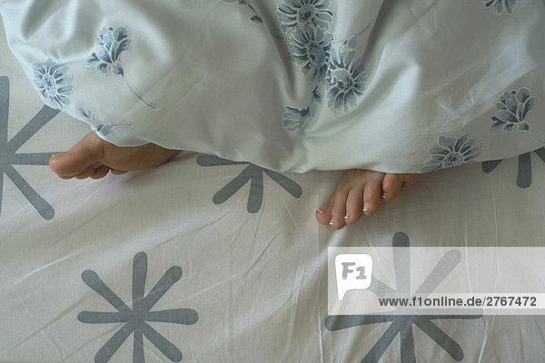 Die Füße der Frau ragen unter der Bettdecke hervor.