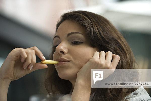 Junge Frau isst Pommes frites  Hand unter dem Kinn