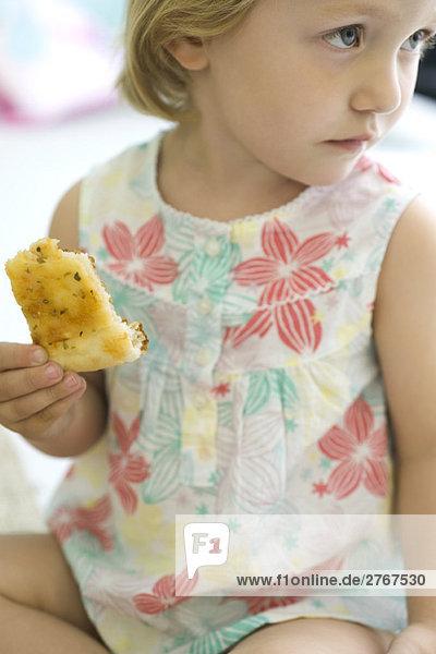 Kleines Mädchen isst Brot  schaut weg.