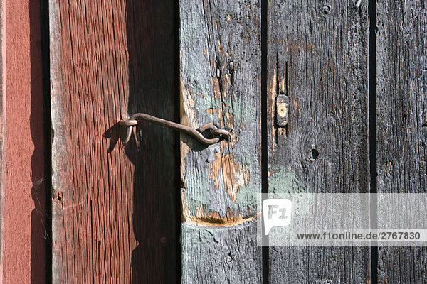 Rusty hook latch on wooden door, close-up YAA085000097