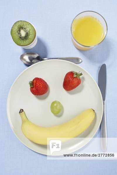still life different fruits on plate forming smiling face