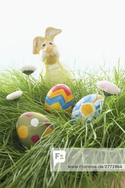 figure of bunny and three painted easter eggs lying in grass