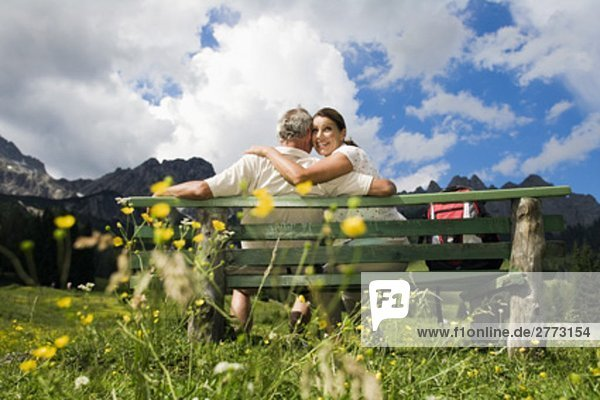 rear view of mature couple sitting on bench in front of mountains
