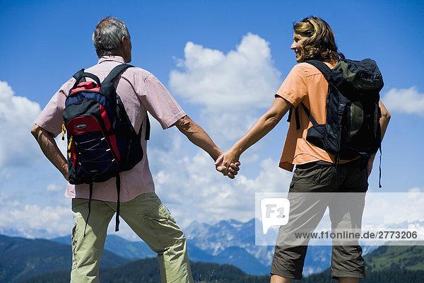 Rückansicht des reifes Paar in den Bergen Hände