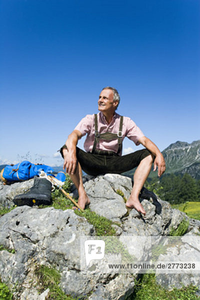 älterer Mann sitzend barfuß auf Felsen in den Bergen