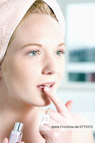 Headshot jungen Frau putting Lippenstift mit Finger auf Mund