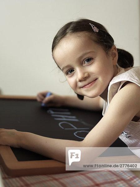 Mädchen an Tafel schreiben