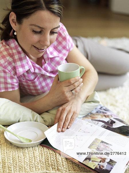 Nahaufnahme Frau lesen Magazine und hält Kaffee cup