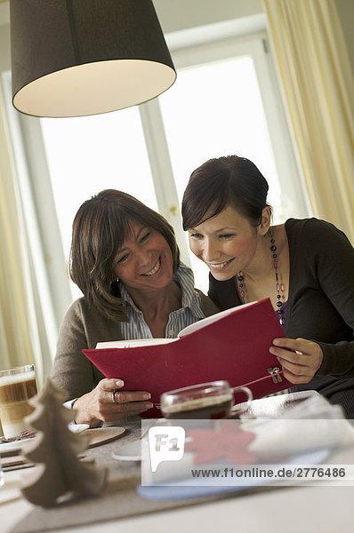 Frau und ihre Tochter Lesung Buch am Frühstückstisch