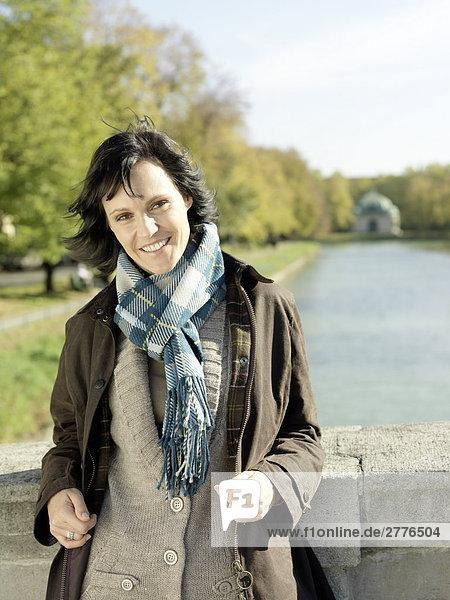 Porträt von Frau auf der Brücke stehend und lächelnd