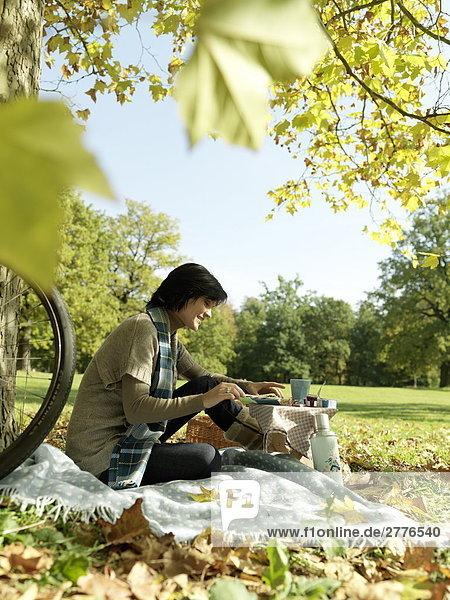 Seitenansicht mature Frau trägt Käse auf Segment im Park auf