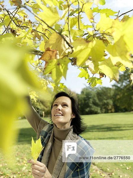 Reife Frau hält Leaf und lächelnd im park