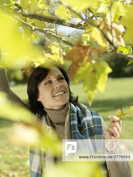 Nahaufnahme frau hält Blatt und lächelnd im park
