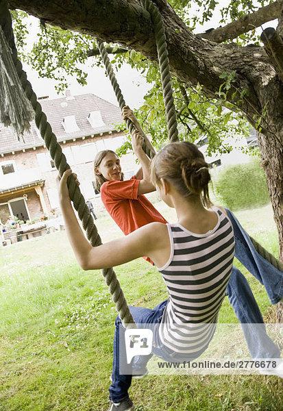 Junges Mädchen und Junge auf einer Baumschaukel