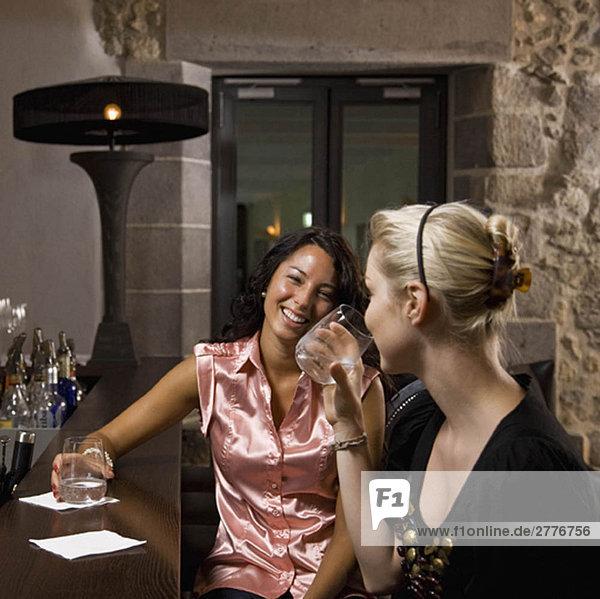 Frauen beim Trinken und Reden in einer Bar