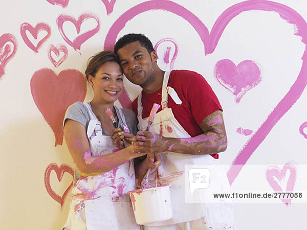 Girl and man in front of pink hearts.