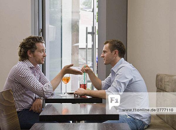Freunde  die am Tisch sitzen und reden.