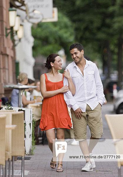 Ein Paar geht die Straße entlang Ein Paar geht die Straße entlang